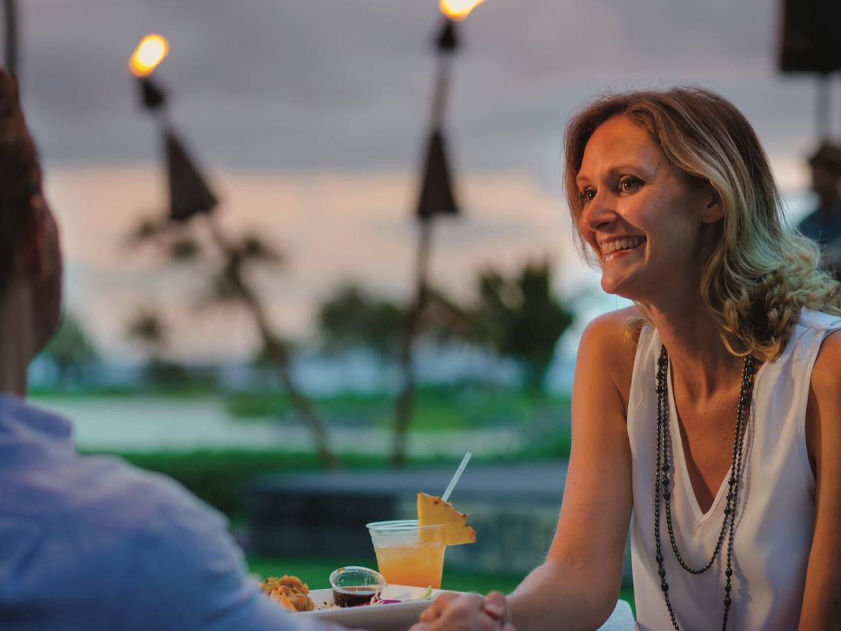 A couple enjoying a meal and a cocktail at an outdoor table by two tiki torches.