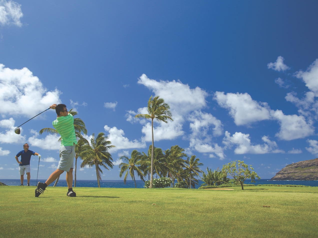 Two friends teeing off at an ocean front golf course. Blue skies and palm trees in the background.