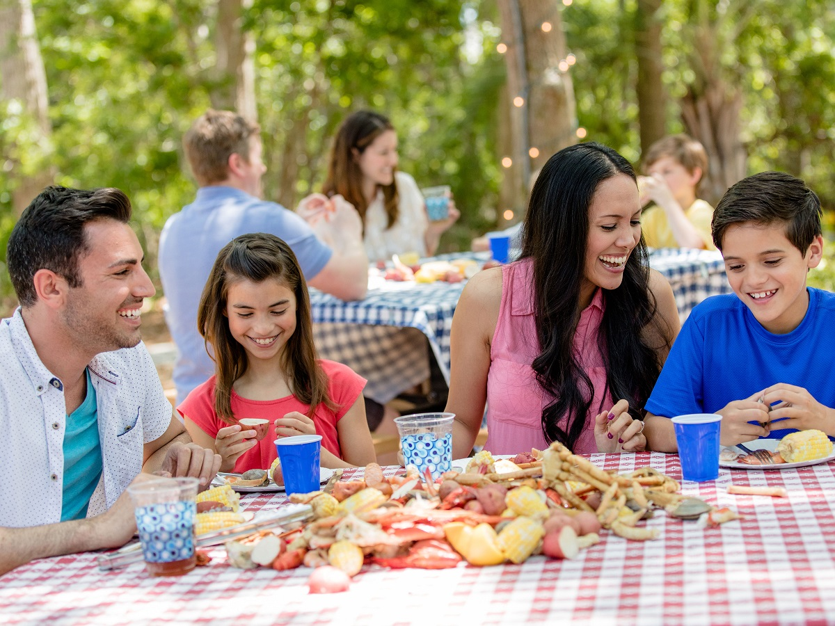 Families laughing and eating at picnic tables outdoors sharing family vacation moments.