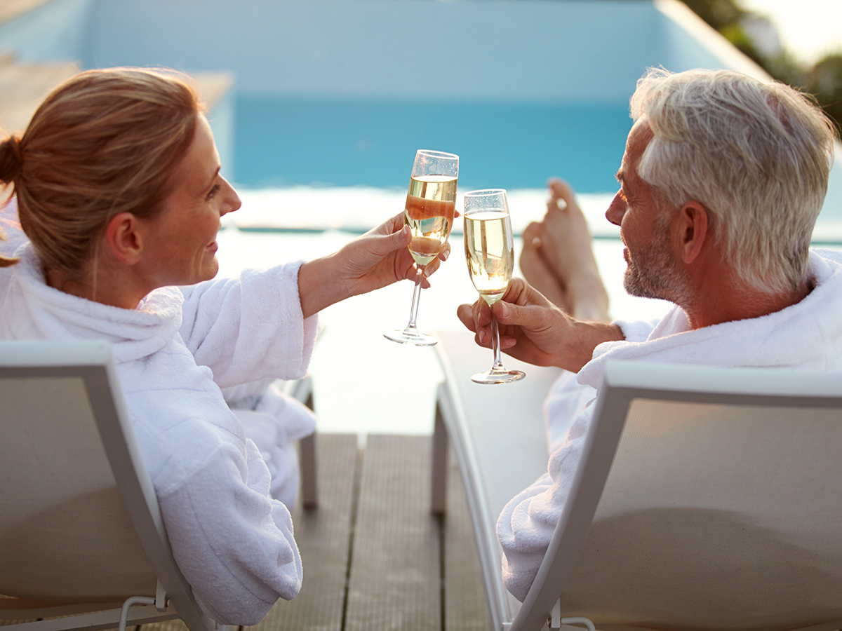 Couple toasting wine at a pool. Vacation your way. Discover the benefits of timeshare ownership.